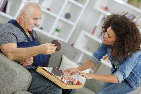 carer-serving-meal-to-injured-senior-citizen-PUSVFY4