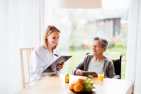 Health visitor and a senior woman with tablet during home visit. A nurse making notes.